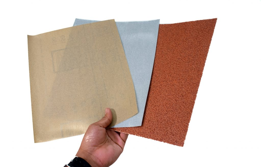 Hand holding 3 sheets of sandpaper