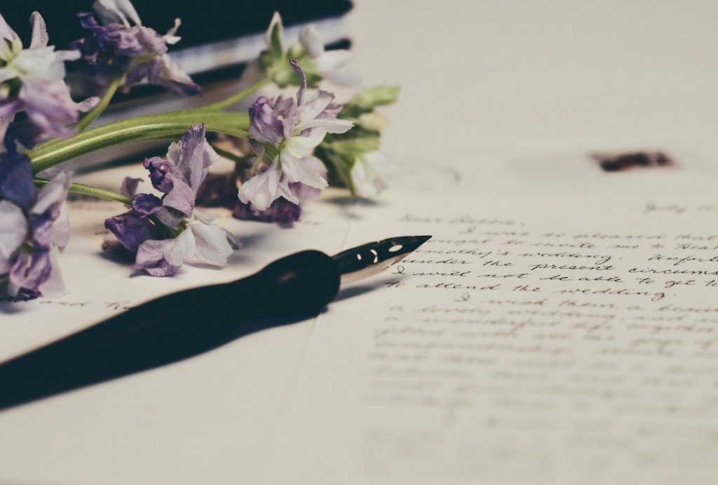 a pen and flower cuttings on a piece of paper