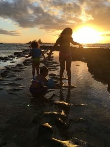 Children playing at the beach at sunset