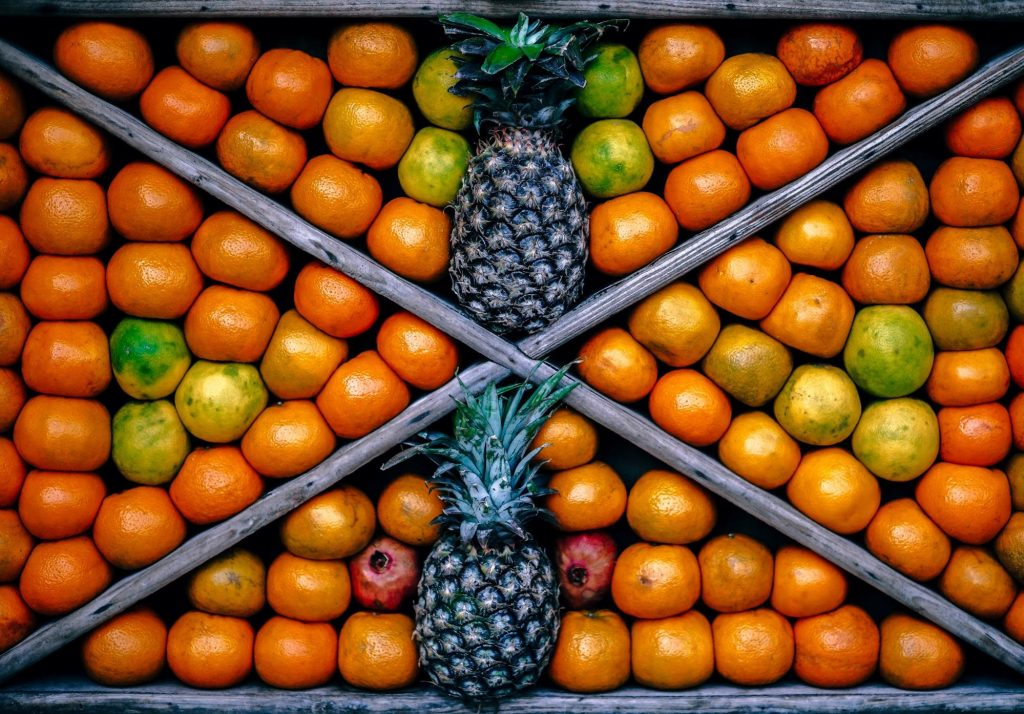 Wooden crate with pineapples and oranges inside