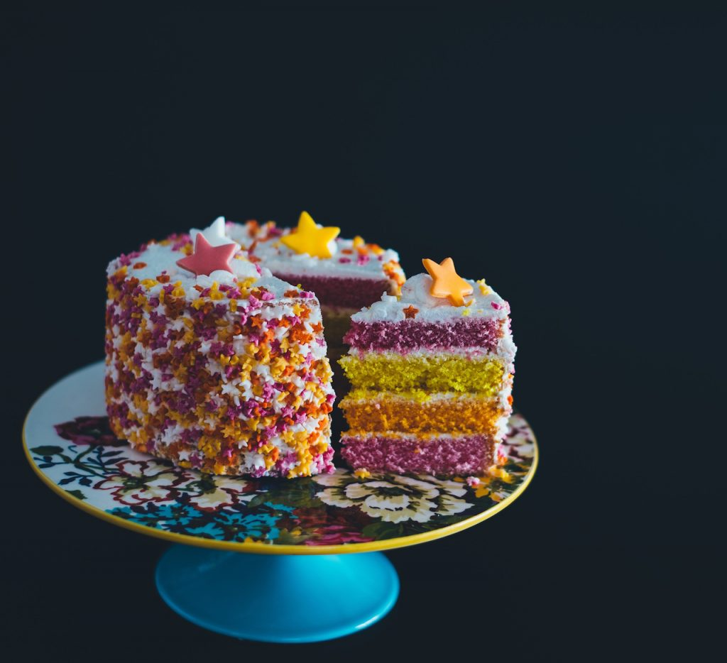 Colorful birthday cake on a cake stand with a slice of cut out