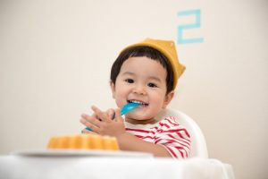 Smiling infant about to eat a cake
