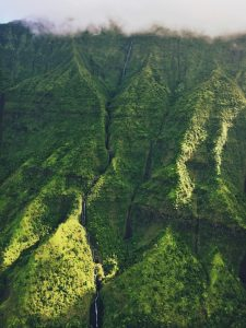 A landscape photo of green mountains top with clouds in Hawai'i