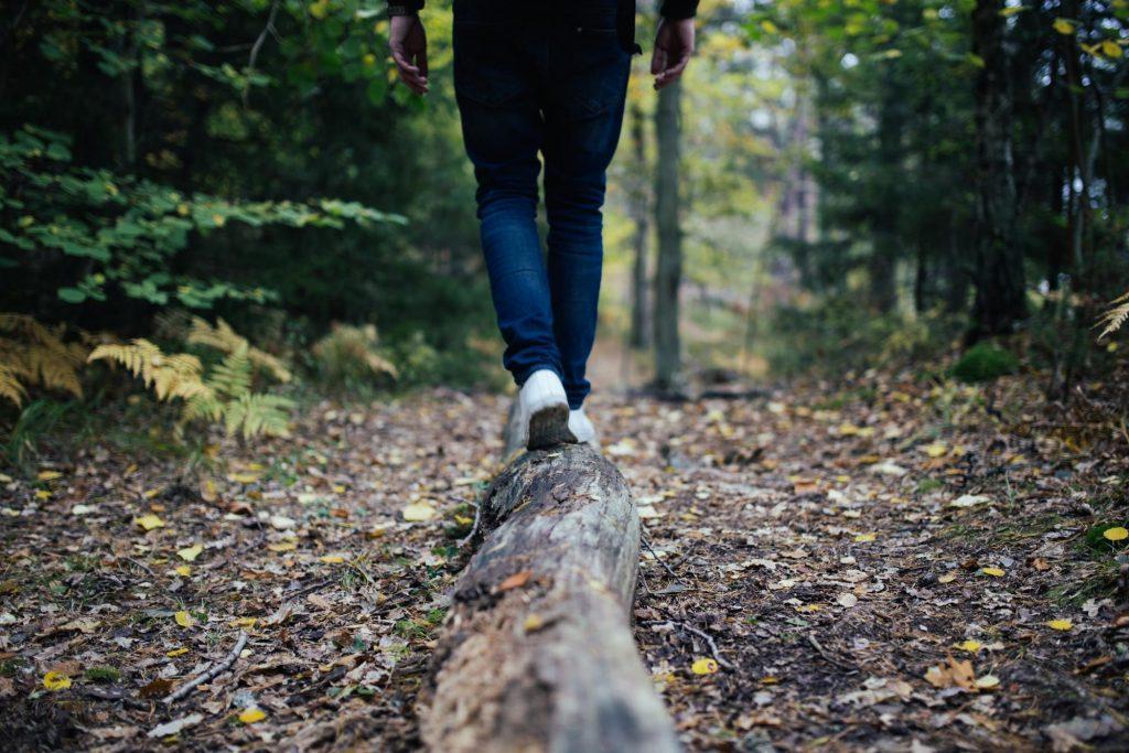 Hiker balancing on log