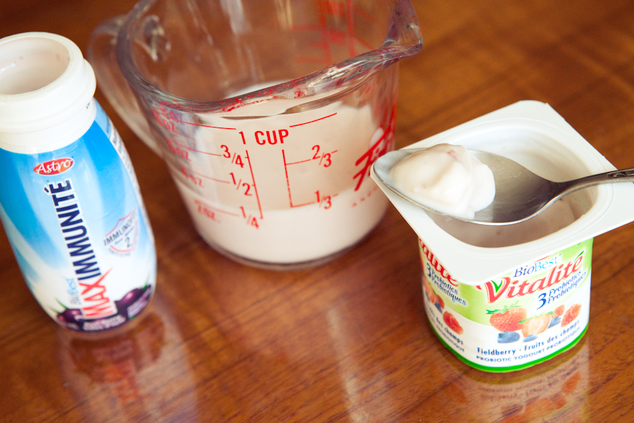 A photograph of a yogurt drink, measuring cup of milk, and a plastic cup of yogurt
